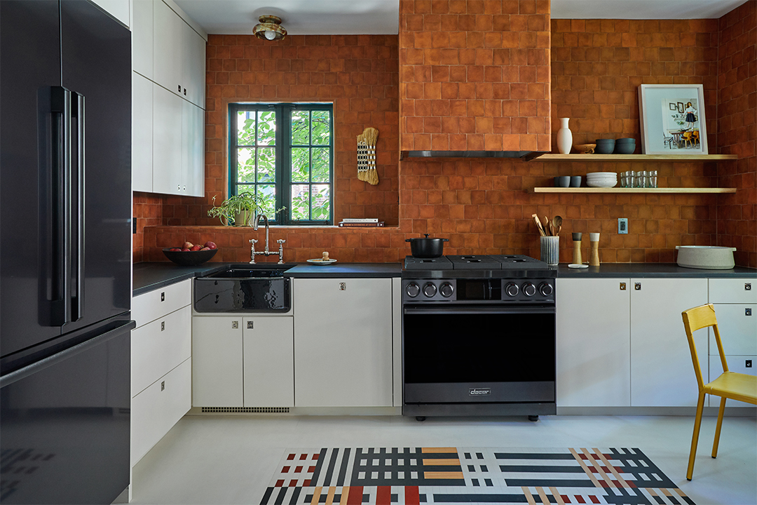 Terra cotta tile wall in kitchen with range and white cabinets