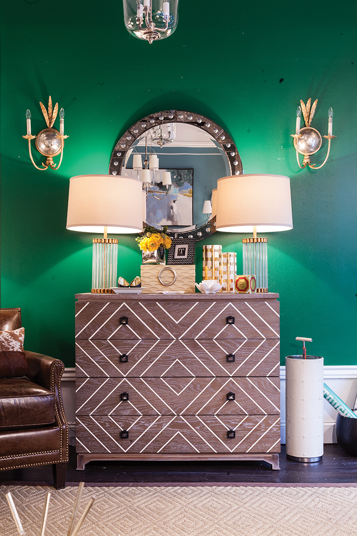 dresser with green walls and lamps.
