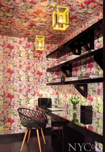 floral wallpapered office with black desk and shells