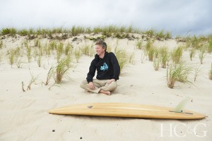 Man sitting cross-legged in the sand in front of wooden surfboard.
