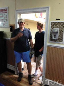 A father and son stand side by side in a doorframe.