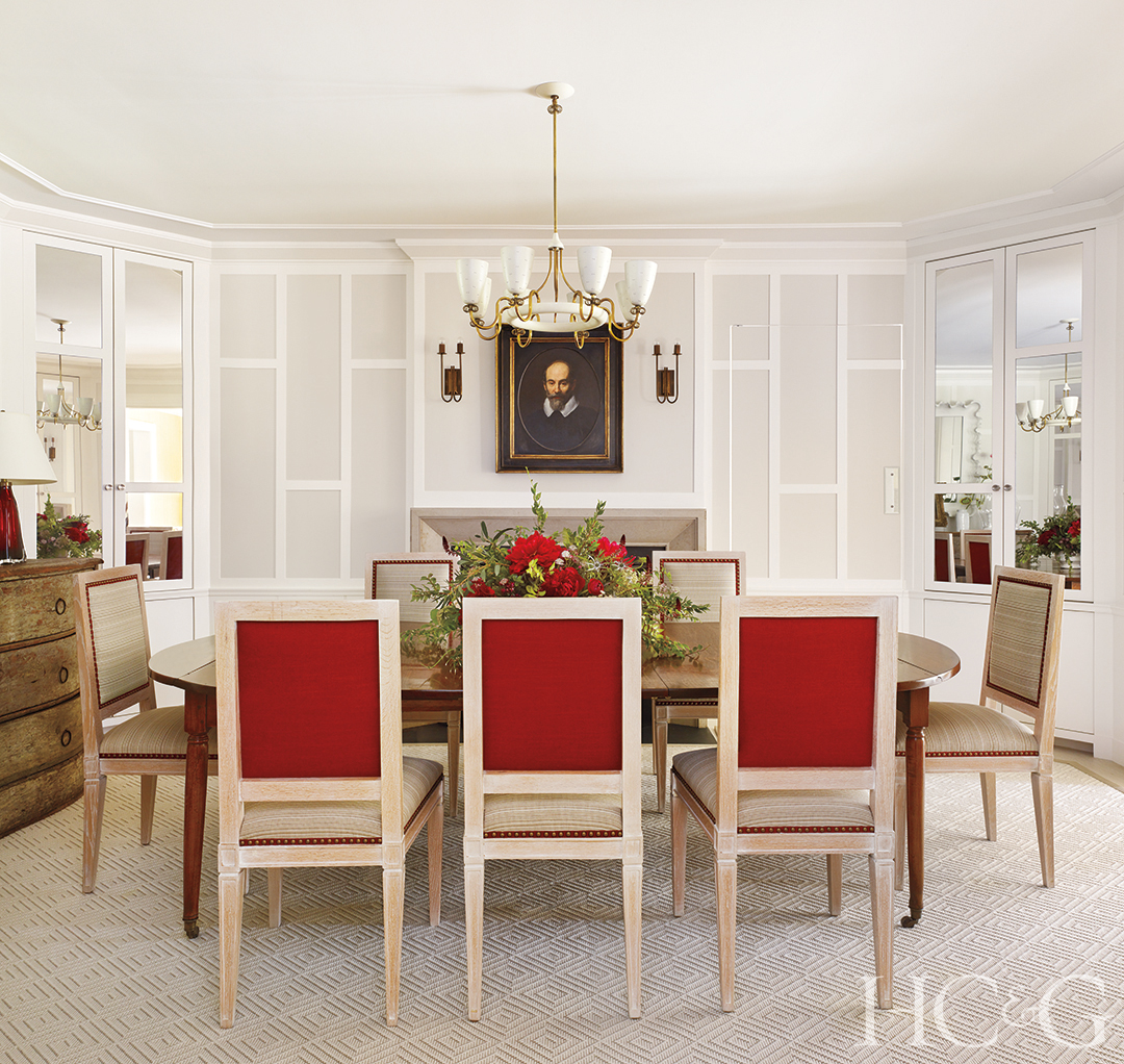 Three red chairs face a dining room table in a white room.
