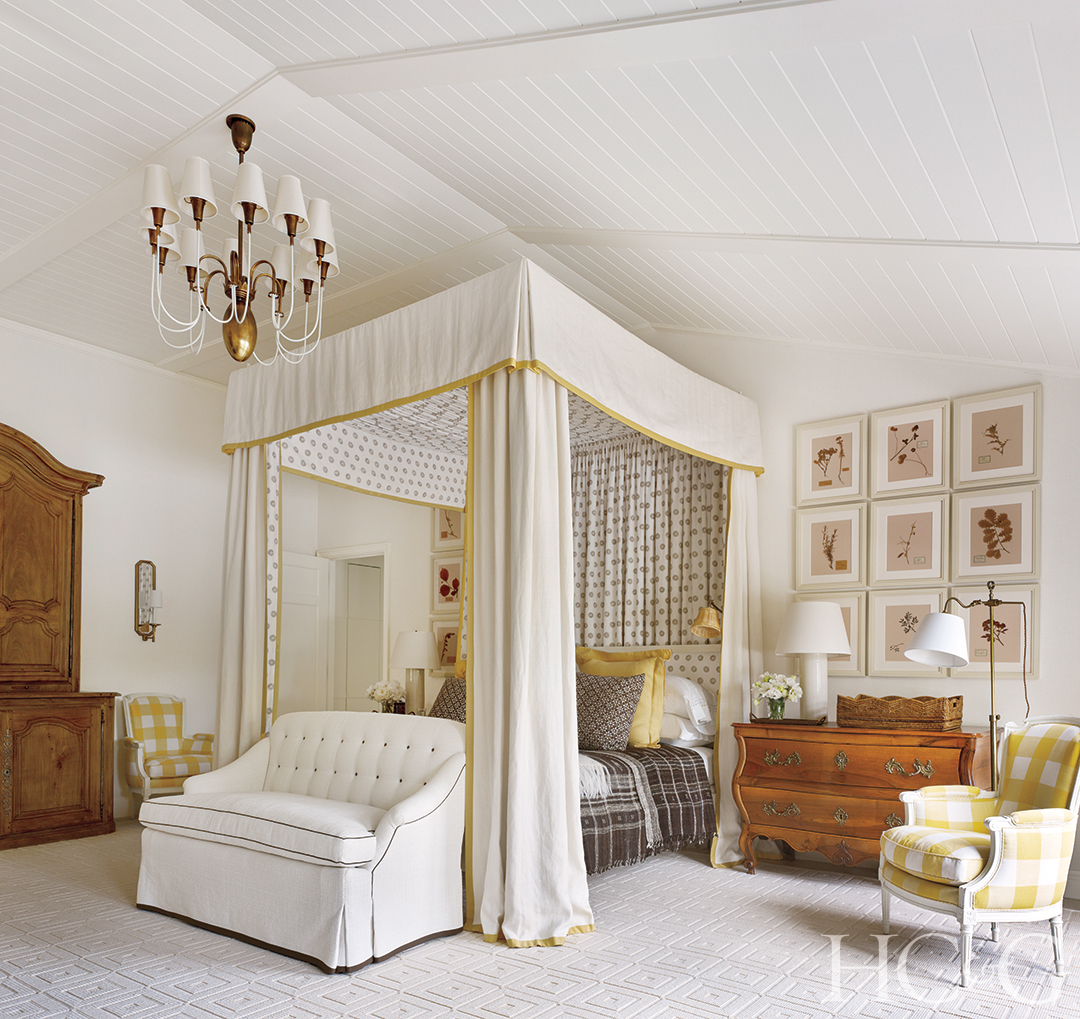 An elegant white canopy with gold trim hangs over a master bed.