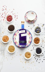 A purple gin bottle on a pink and blue plate.