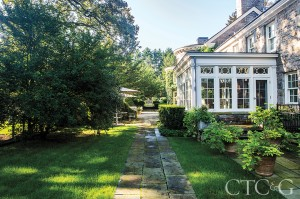 A stone path leads alongside the sunroom and potager garden.