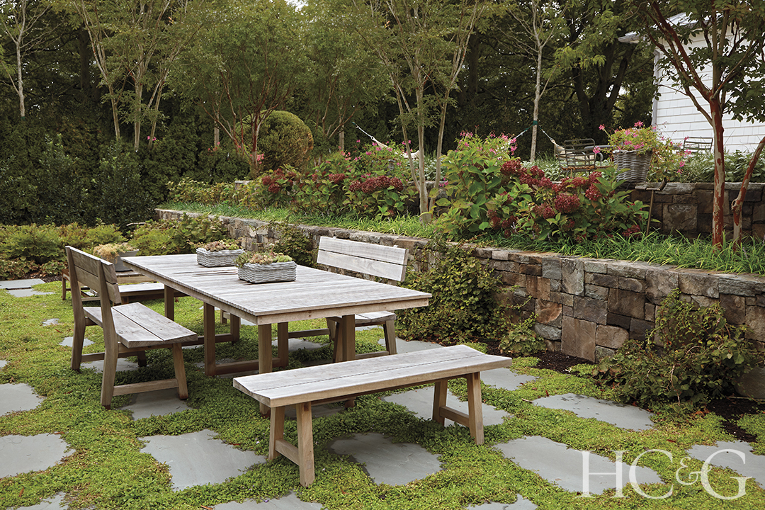 Wooden benches surround a wooden table outdoors.