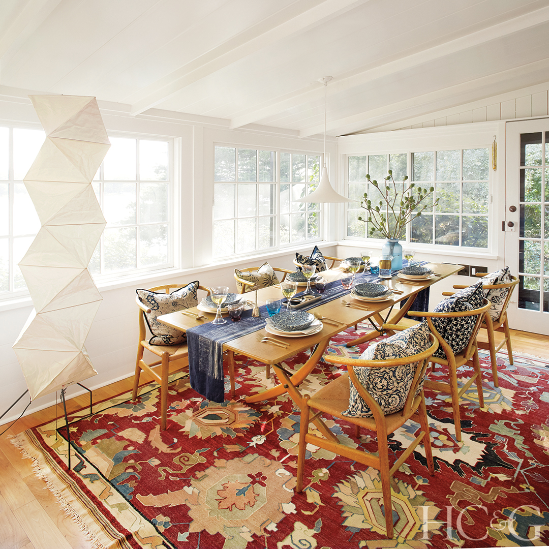 A red carpet brings color to a white dining room with wooden chairs and table.