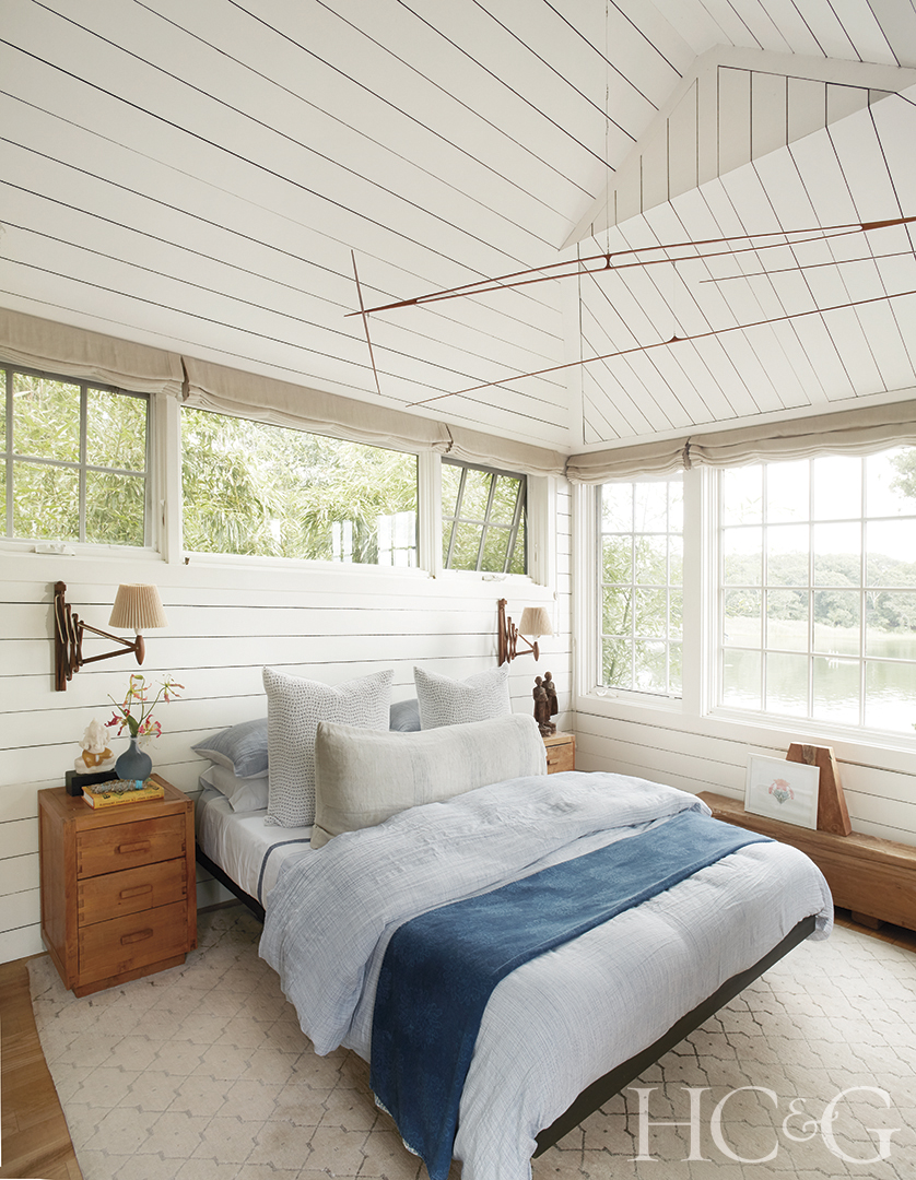 A white master bed with blue accenting between two wooden night tables. The bed is surrounded by bright windows and white walls.