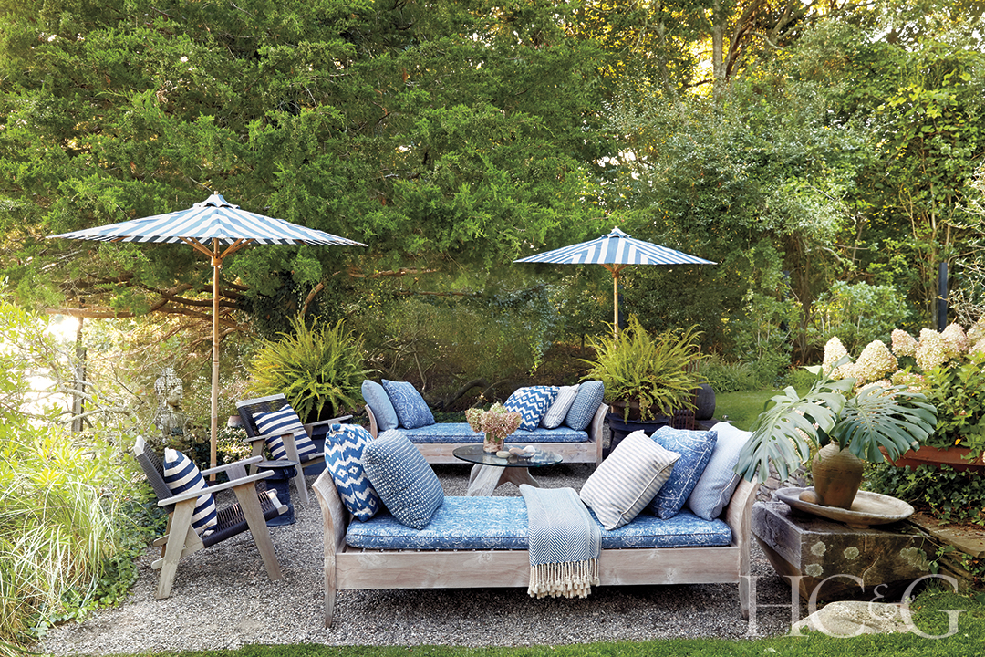 Outdoor chaises cushioned in blue are accompanied by blue lounge chairs and umbrellas in contrast to the green foliage.