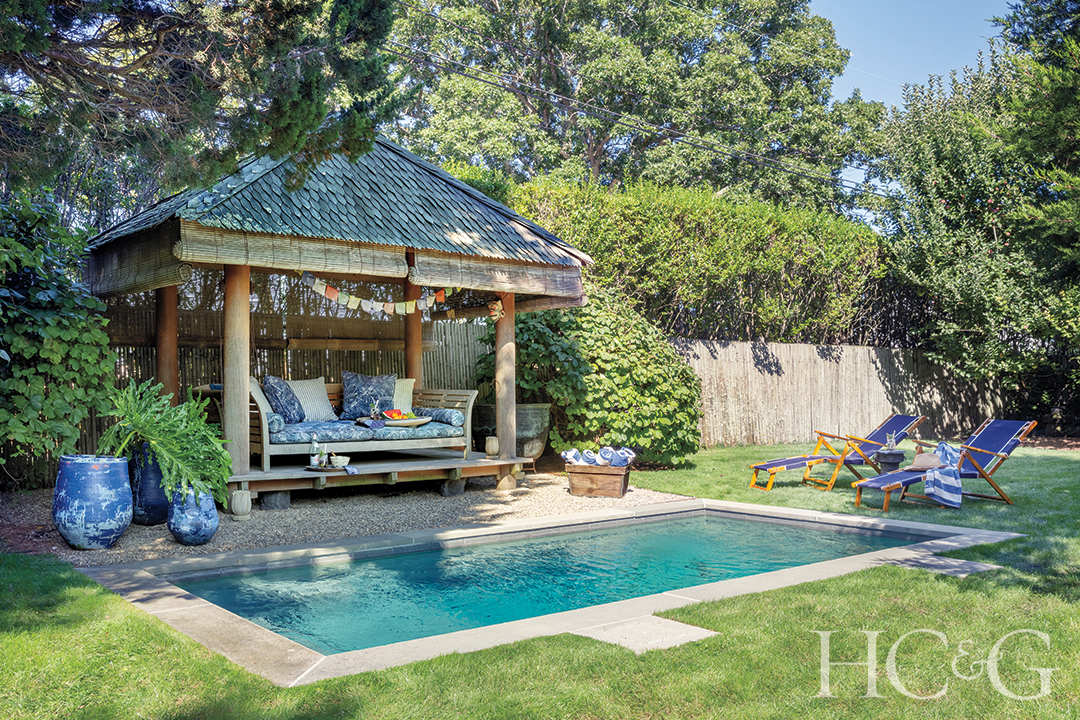 An iron and wood gazebo sits behind a rectangular swimming pool.