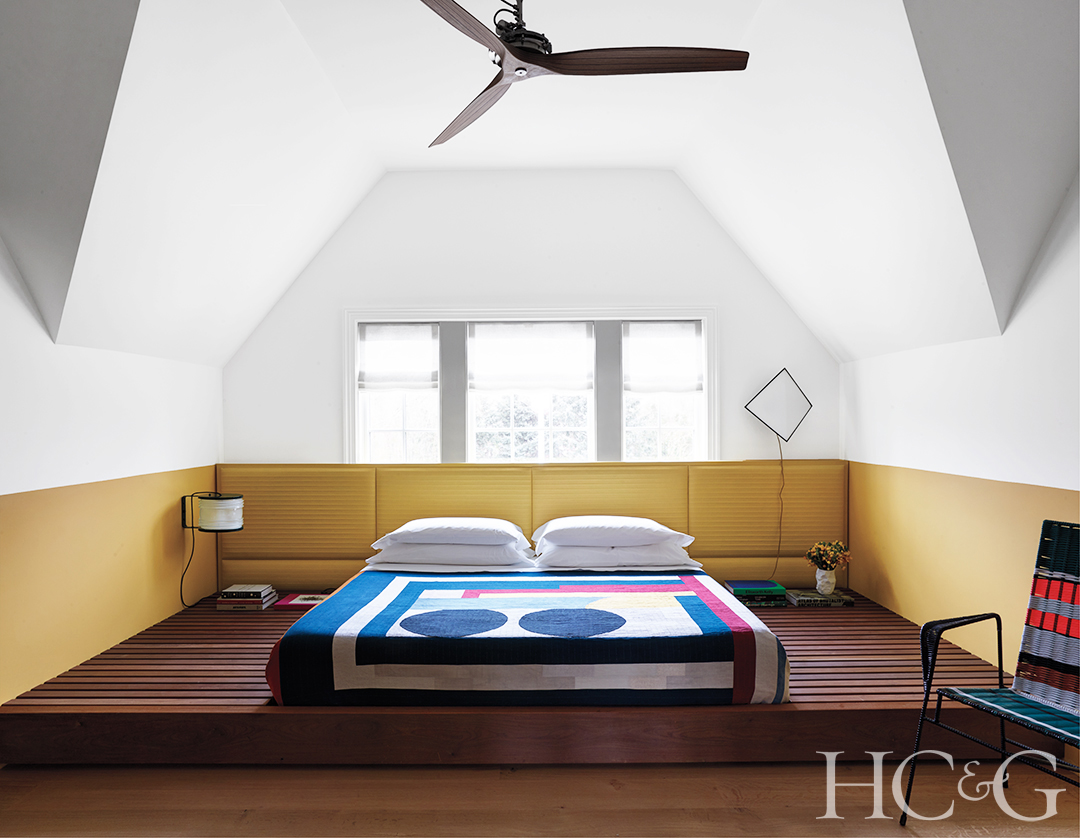 A full bed surrounded by a split yellow and white wall.