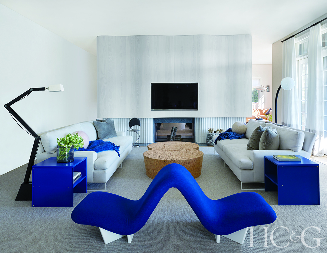 A royal blue banquette flanked by two sofas.