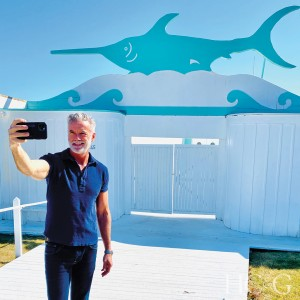 A man in a blue shirt takes a selfie in front of a nautical exterior with a blue swordfish painted on the top.