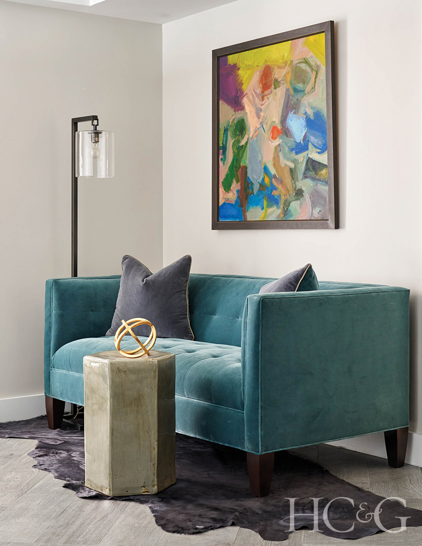 A teal blue couch with an abstract painting on the wall.