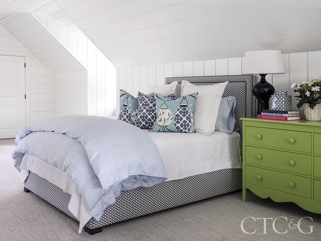 green chest sits next to blue patterned comforter and pillows atop custom bed in the bunk room