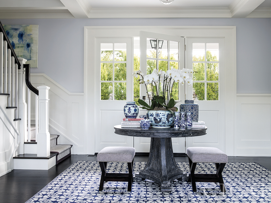 custom stools and cerused oak table and decor atop blue patterned rug create eye-catching entry