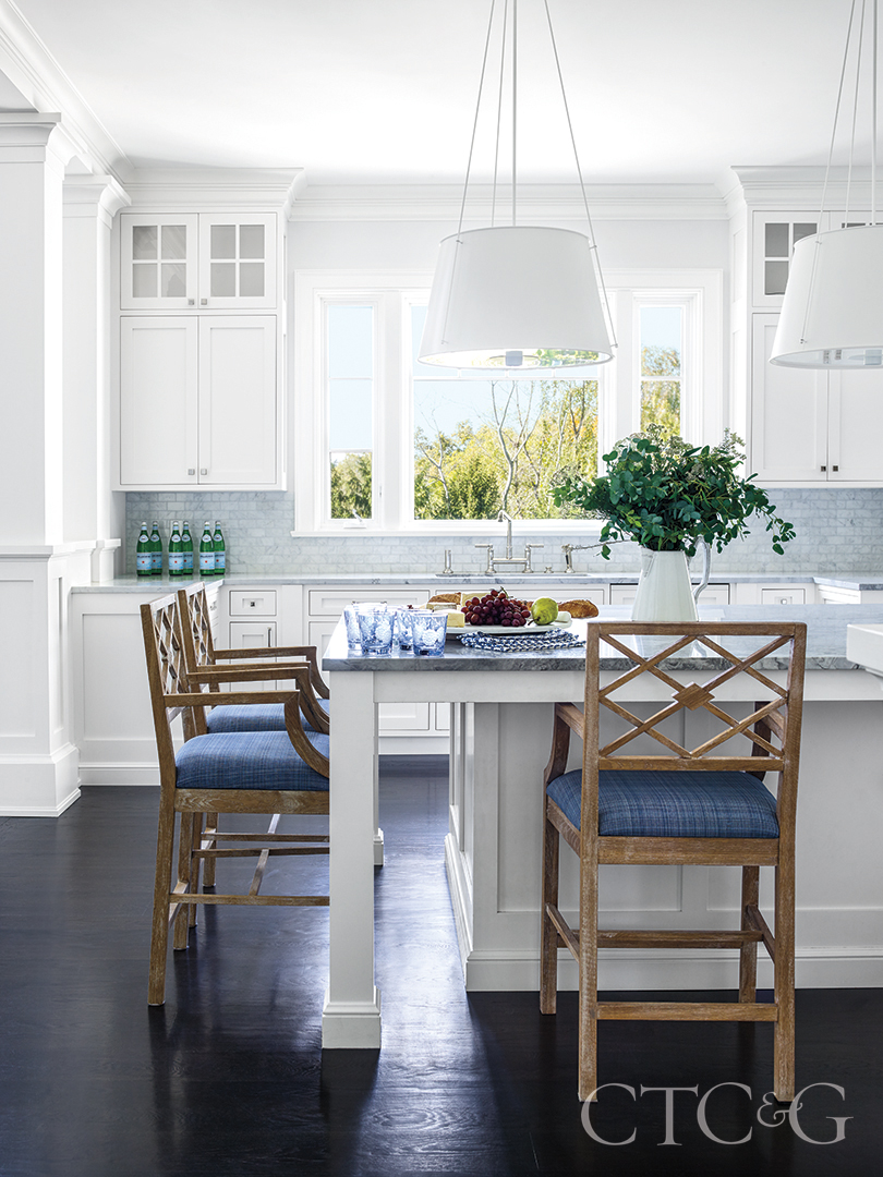 natural light highlights the white marble kitchen and complimentary blue cushioned oak island chairs