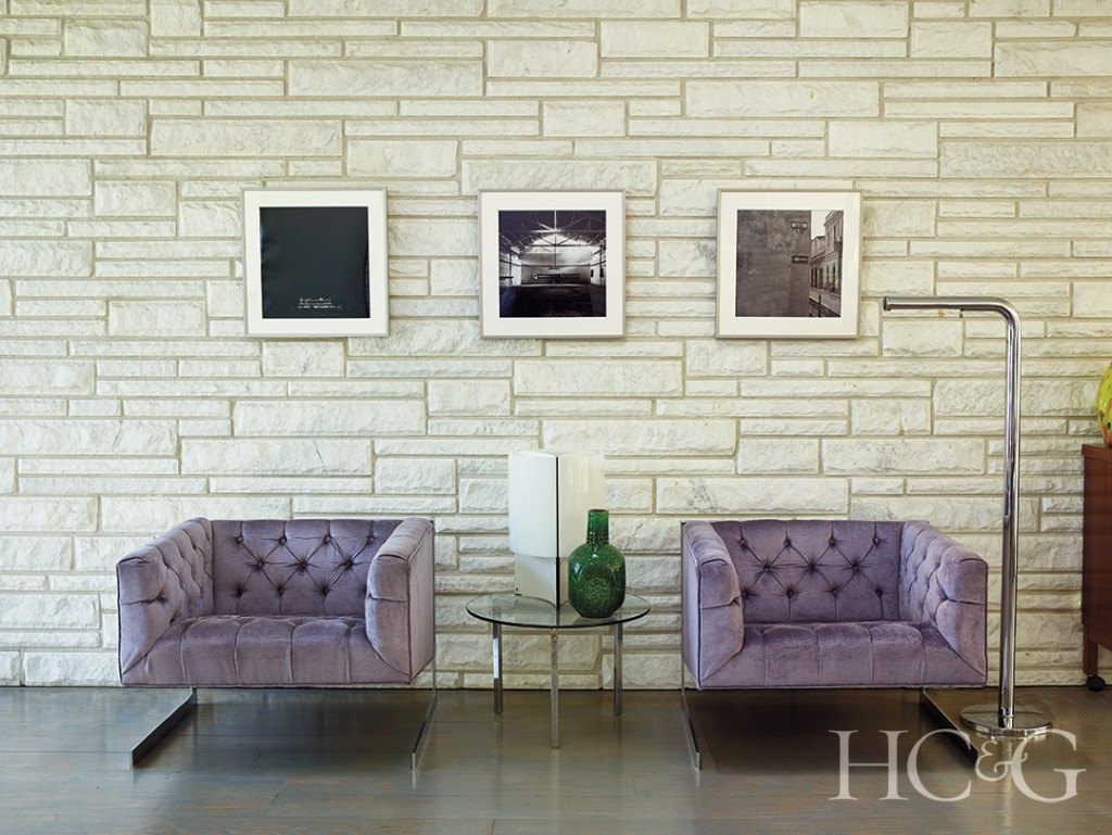 Tufted armchairs and stone wall