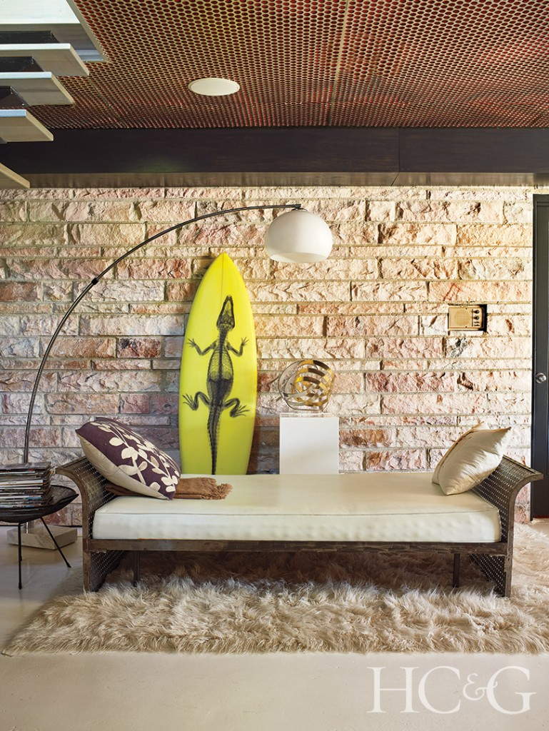 Vintage Metal Daybed and Overhead Lamp with Stone Wall and Yellow Surfboard