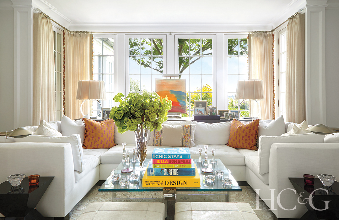living room with custom white sofa and accent pillows; decorative table lamps and coffee table books