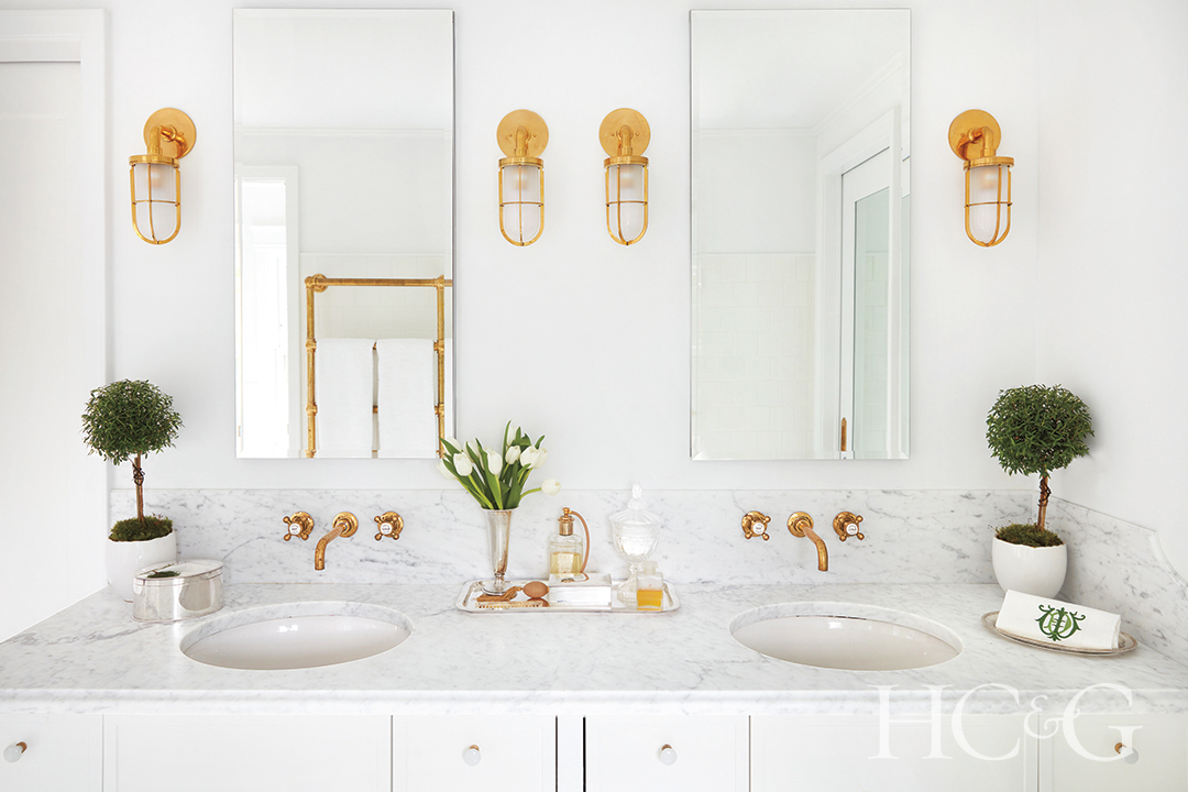 mirrored medicine cabinets and golden sconces in main bathroom