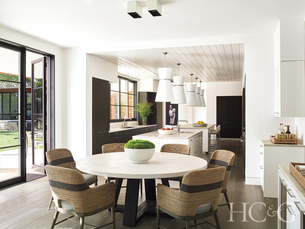 custom islands in kitchen, round concrete table, rope chairs, and cabinetry