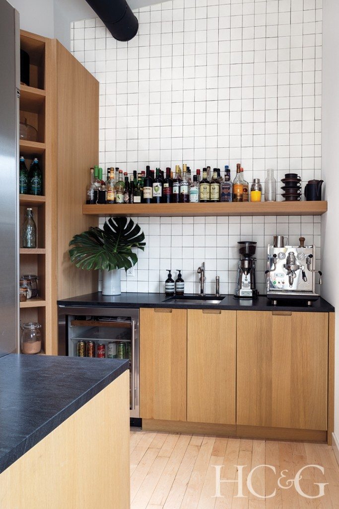 wood cabinetry, refrigerator, and wine refrigerator; white backsplash tile