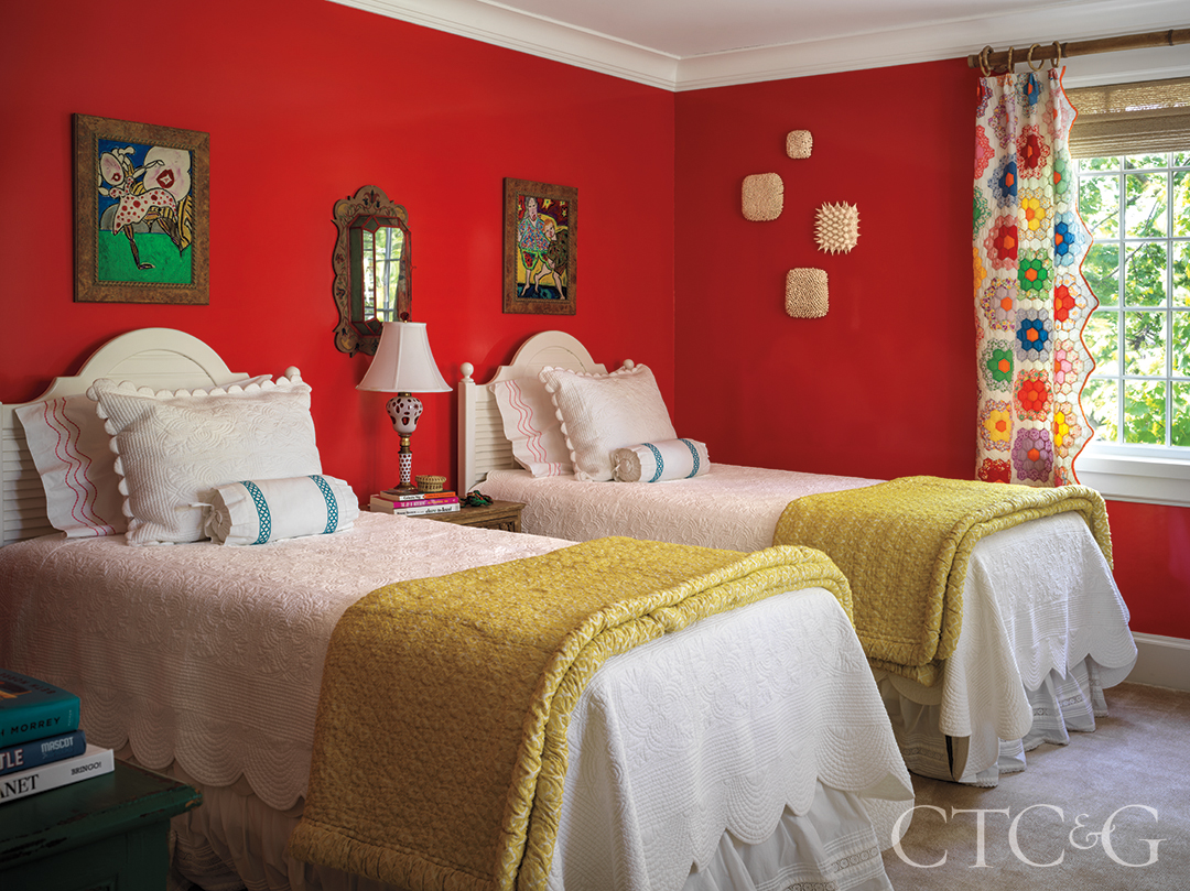 framed artwork in guest bedroom; wall sconce and twin beds dressed with green quilts