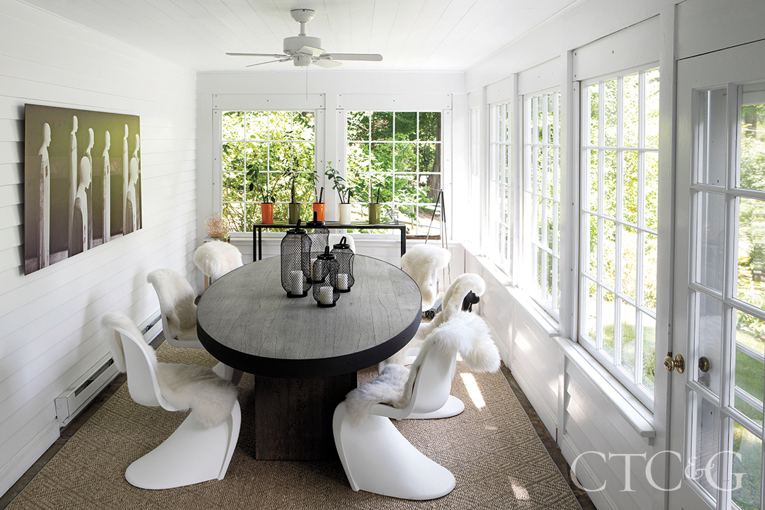 panton chairs with sheepskins and custom oak-and-steel table in sunroom
