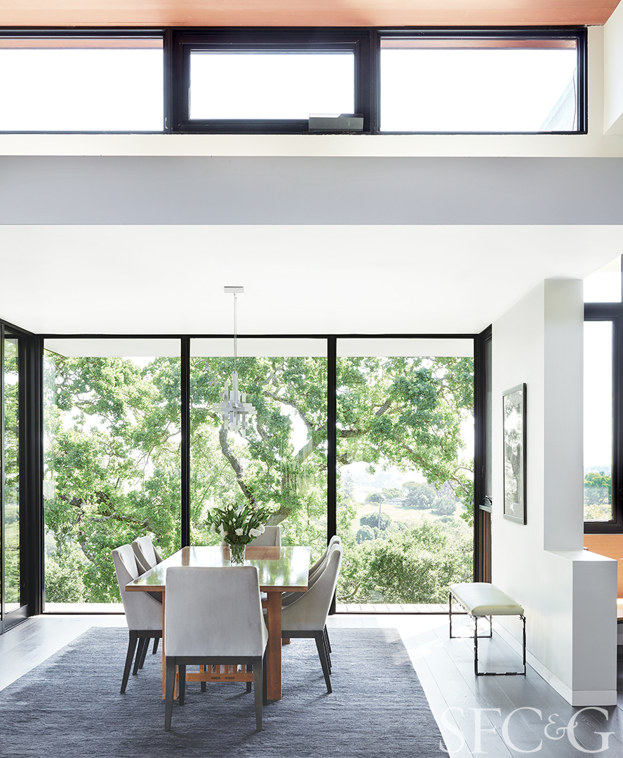 Field designed the home to feel embraced by the surrounding oaks. The dining room pendant is by Sonneman; Paul Ferrante's Dante bench is from Hewn.