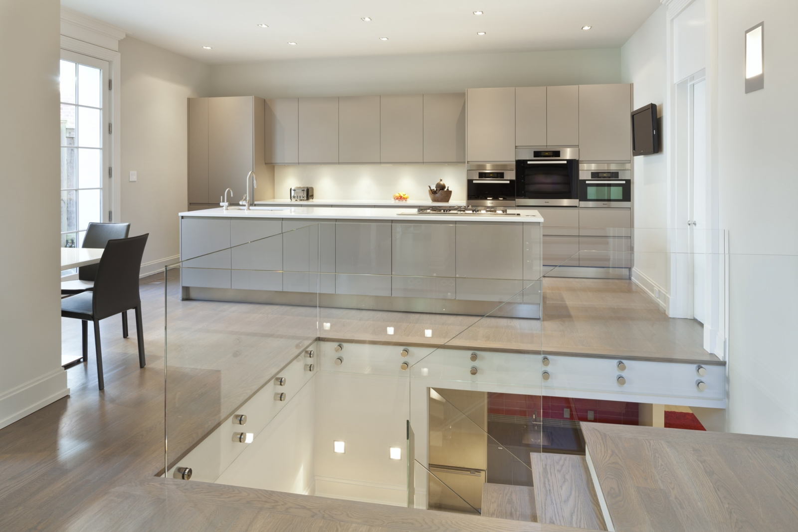 A contemporary glass staircase leads up to the kitchen.
