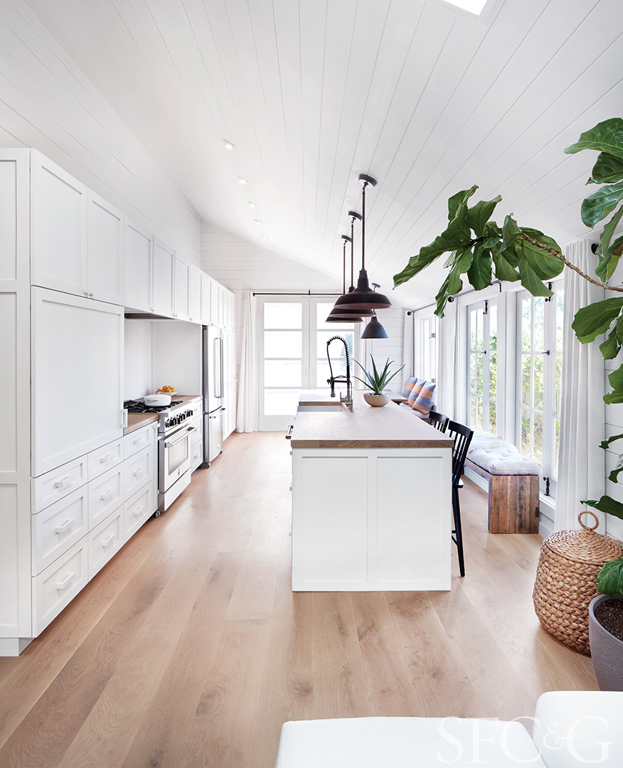 The heart of the home features an adjoined living room and kitchen, making the room feel open and spacious. White oak countertop is through Mount Storm Forest Products. A Blanco farmhouse sink is complemented by a Ruvati faucet. Barn pendant lights are through RH.