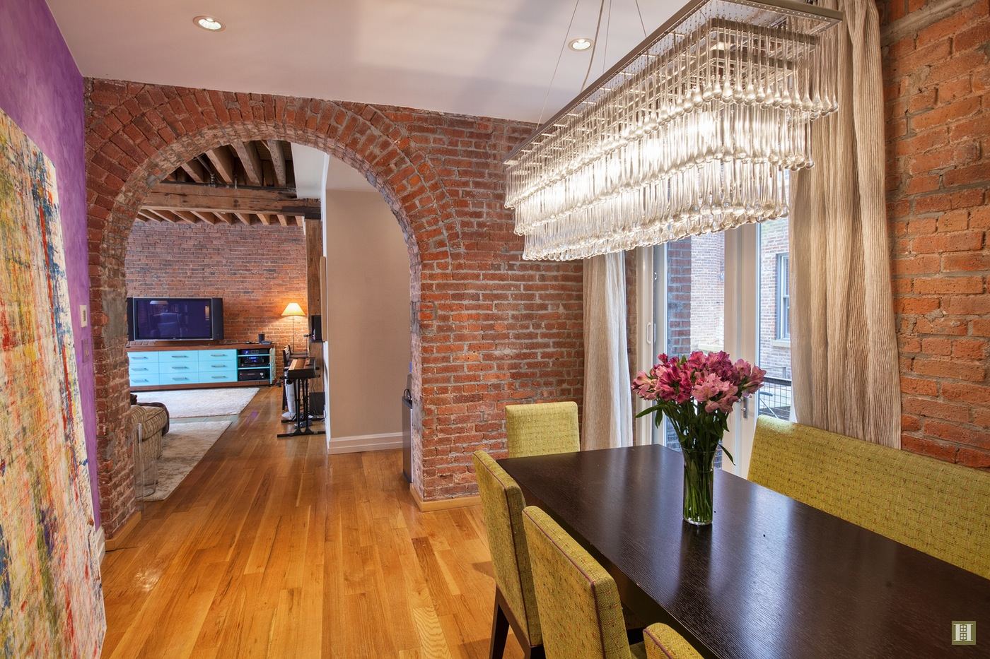 A dramatic brick archway leads from the dining room into the living room.