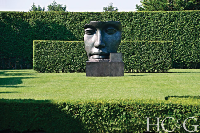 Double privet hedges create a striking background for an oversize bronze head by Polish sculptor Igor Mitoraj.