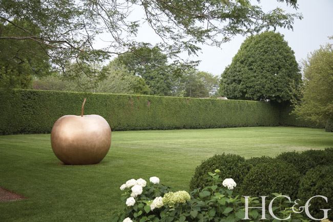 Pomme, a witty, oversize gilded bronze sculpture by Les Lalanne, graces the lawn at the Bridgehampton home of interior designer Alex Papachristidis.