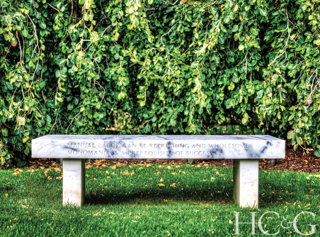 A 1987 marble Truisms bench by Jenny Holzer sits in front of a weeping beech.
