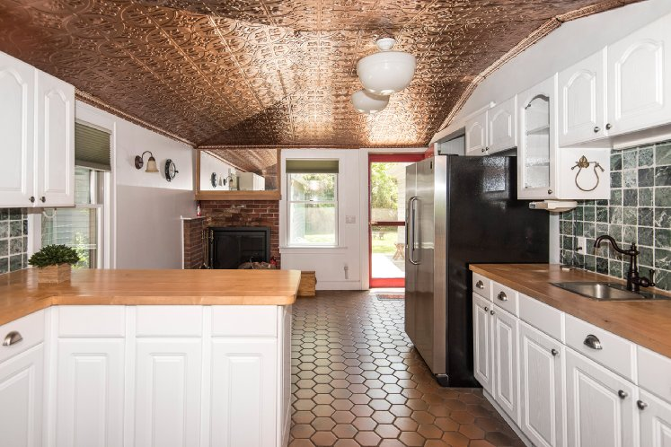 The country kitchen features tin ceilings.