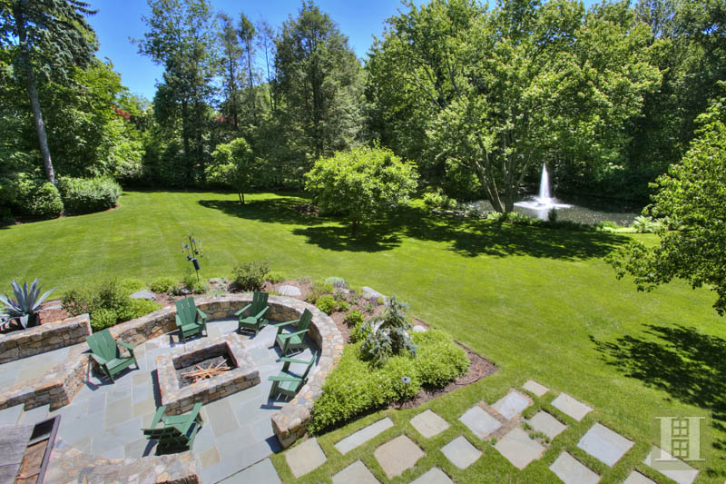 The landscaped property features a stone patio and firepit.