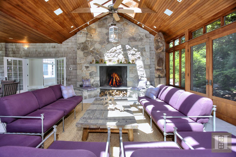 The screened-in sun room features a stone fireplace.