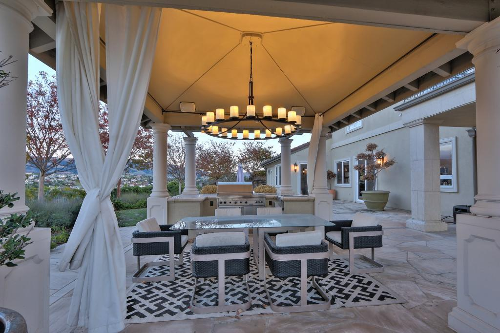 A covered al fresco dining space features an outdoor kitchen.