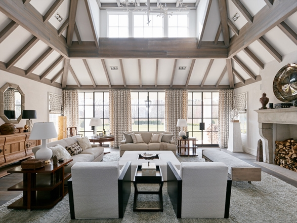 The living room makes a statement with a double-height ceiling accented with wood beams.