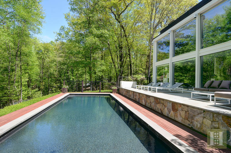The two-story glass wall overlooks the pool.
