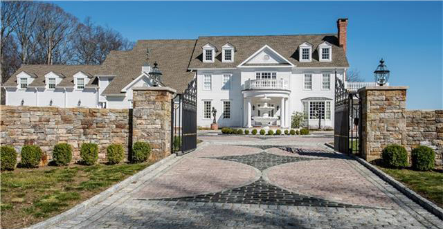 A gated driveway leads to the elegant Georgian Colonial home.