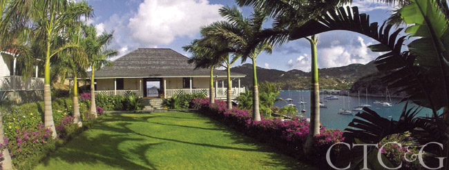 A waterfront home in St. Barthelemy with a green yard and palm trees.