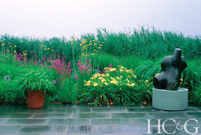 A tapestry of flowering perennials, including daylilies and liatris, creates a lush backdrop to a Henry Moore bronze
