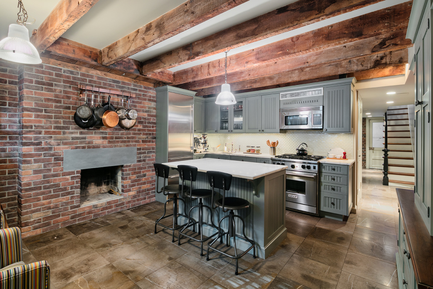The kitchen features exposed beams and brick as well as Sub-Zero and Viking appliances.