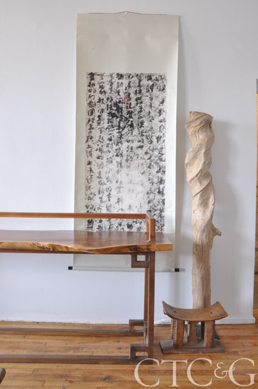 A teak tree sculpture and a 19th-century African chief's stool