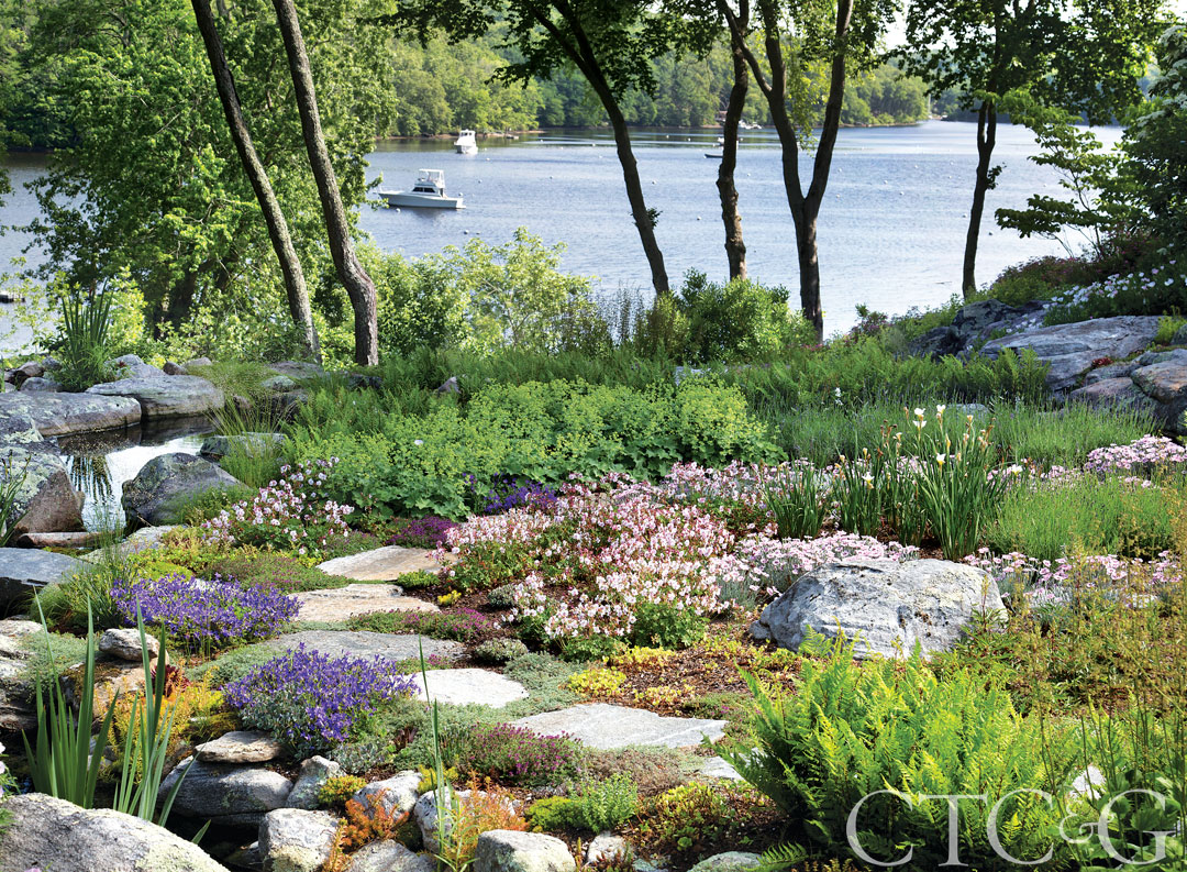 The picturesque cove is visible throughout the property. A pathway through the rock garden passes by plantings of Lady's Mantle, Norther Lady Fern, geranium 'Biokovo' and astilbe.