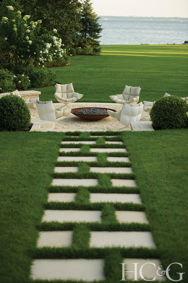 A limestone pathway featuring grass joints leads to a sunken terrace with views of Long Island Sound.