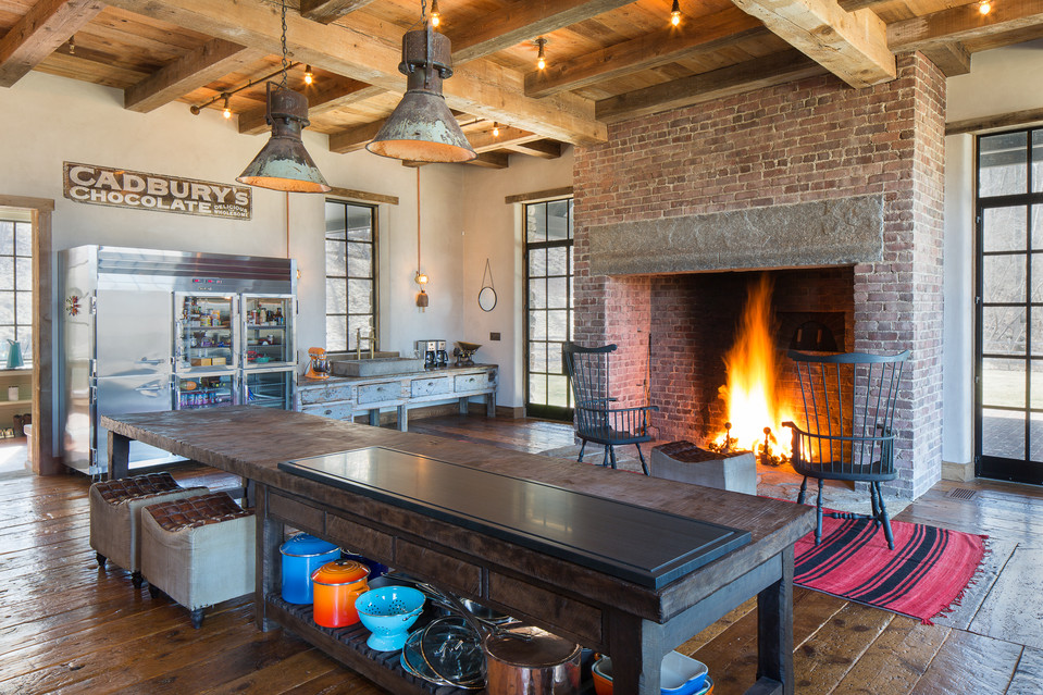 The eat-in kitchen features a grand fireplace and pizza oven.